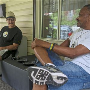 "Veterans Hugh D. Walker Jr., left, Dave Matta, center, and Kenneth Williams, right, talk on the porch of their ""veteran rehabilitation home,"" which was started by former Probation Officer Dante Works, Friday, July 27, 2018 in Homewood. Works bought and renovated the home to assist veterans who are in the last process of ""graduating"" from Veterans Court in hopes that this would be a safe and comfortable environment for men to stay while getting back on their feet."