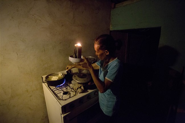 """In this Aug. 19, 2018, photo, Mireya Marquez uses candlelight to cook her dinner of boiled """"cassava,"""" also known as yuca and manioc, during a blackout in Maracaibo, Venezuela."""