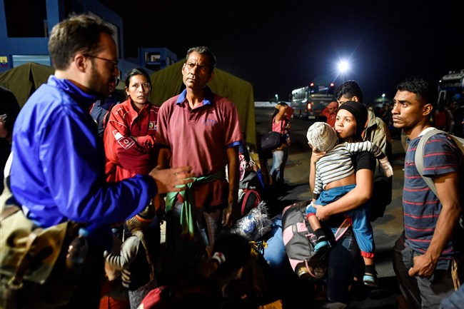 "A UNHCR official speaks with Venezuelan migrants Aug. 25, 2018, upon their arrival in Huaquillas, Ecuador, on the border with Peru, after touring in buses facilitated by the Ecuadorian authorities as part of a ""humanitarian corridor"" to facilitate the passage of Venezuelans who migrated due to the economic crisis in Venezuela."