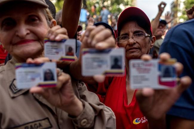Demonstrators display Carnets de la Patria, or Fatherland identification cards, in Caracas, Venezuela, on Aug. 21, 2018. MUST CREDIT: Bloomberg photo by Manaure Quintero.
