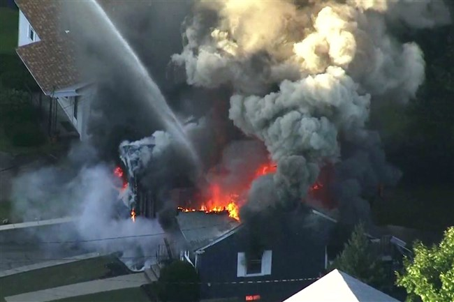 In this image take from video provided by WCVB in Boston, flames consume the roof of a home in Lawrence, Mass., a suburb of Boston, on Thursday.