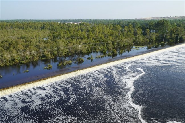 In this drone photo released by Duke Energy, flooding from the swollen Cape Fear River overtops an earthen dike at Sutton Lake, a 1,100-acre lake at the L.V. Sutton Power Station near Wilmington, N.C., on Thursday, Sept. 20, 2018.