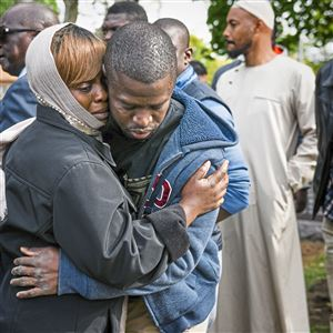 Bukky Ogunsola, left, comforts Abdullahi Aminu after he'd buried his uncle Abdulganiyu Sanusi at Chartiers Cemetery in Carnegie on Tuesday, Oct. 16, 2018.