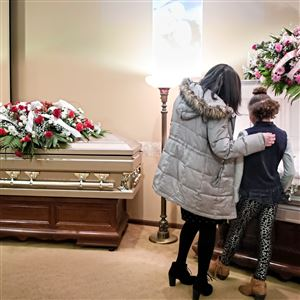 "Zayah Pumphrey, 9, is comforted by her first-grade teacher, Stacy Henry, left, of New Castle, as they visit the casket of Zayah's 10-year-old sister, Amariah Emery, beside the casket of her mother, Nichole Pumphrey, on Sunday, Oct. 21, 2018, at J. Bradley McGonigle Funeral Home and Crematory, Inc. in Sharon. While Zayah was standing with Ms. Henry at her sister's casket, she was asked by her cousins why her mother's casket was closed. ""She said, 'I don't think you'd want to see her. It would make you sad,'"" said Ms. Henry, recalling the conversation."