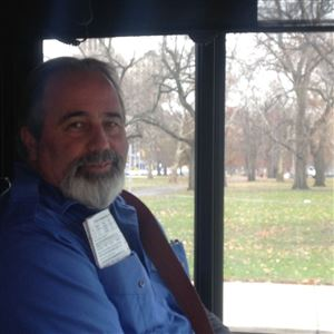 Tim Sheerer, in the driver's seat of the 54D , with ALlegheny Commons Park in the background.