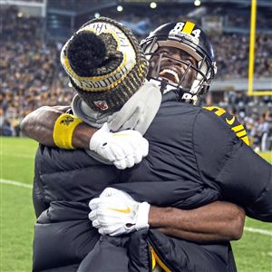 Antonio Brown hugs injured running back James Conner after Brown's touchdown against New England on Sunday.