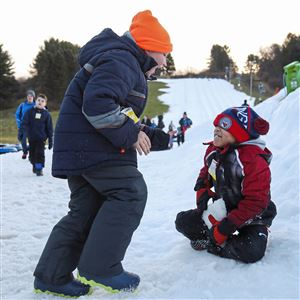 Friends Kole Bearclough, 9, of Ellwood City, left, and Koby Washington, 7, of Monroeville, right, play in the snow together after a day of snow tubing Dec. 30, 2018, at Boyce Park in Plum.