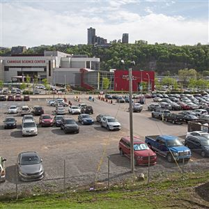 Cars park in an unpaved lot across from the Carnegie Science Center Wednesday, April 24, 2019, on the North Shore. The development of the surface parking lot has recently been given a time limit by the Pittsburgh Parking Authority.