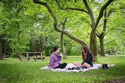 Sophia Thiros, 19, of Carnegie, and Miya Sparbanie, 19, of Squirrel Hill, spend time together on a blanket at Frick Park on On Wednesday in Point Breeze.
