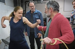 "Dana Hardy Bingham, left, prepares to punch Ken Bolden, portraying the Duke of Gloucester, while Pittsburgh actor and fight coordinator Randy Kovitz, center, supervises during a rehearsal for Quantum Theatre's ""King Lear"" in Swissvale. Director Risher Riddick, right, looks on."