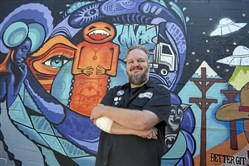 "Matthew Buchholz, DJ and creator of ""In Bed by 10"", a dance party/fundraising event series that is focused on the over-30 crowd that want to party but also be ""in bed by ten.""  In front of the mural on Spirit in Lawrenceville."