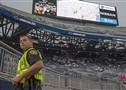 The game has been postponed as an officer stands underneath the jumbotron monitoring a storm system before the game on Saturday, Sept. 14, 2019, at Beaver Stadium in State College.
