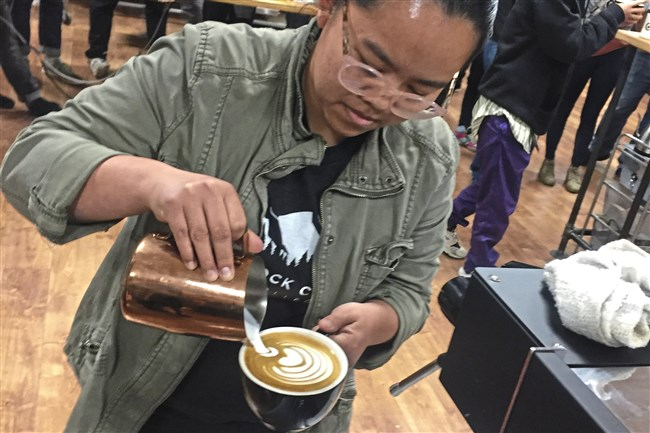 Joyce Yong of Rothrock Coffee in State College pours a latte at 2018's Pittsburgh Coffee Week's Latte Art Throwdown. Yong won last year's competition.