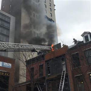 Firefighters work to extinguish a four-alarm blaze at a building in Market Square, Downtown that houses the Winghart's restaurant, on Thursday around lunchtime.