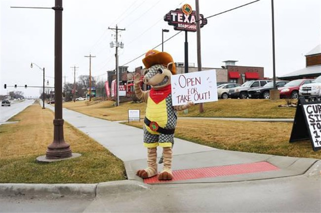 "A Texas Roadhouse mascot displays the sign ""Open for Take Out"" in front of the restaurant in Ames, Iowa, on March 18, 2020."